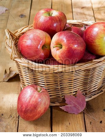Basket of red apples on a wood surface