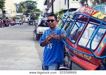 05 Aug 2017 Dumaguete Philippines: a local tricycle driver by his vehicle. Local man on driver job. Low-paid work. Public transport. Tourist sightseen. Philippines symbol tricycle. Urban transport