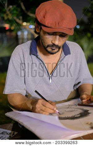 Dhaka, bangladesh, august 2017-a young indian man with hat drawing people face at street at night near hatiljhil bridge Bridge in dhaka in bangladesh taken on 7, september 2017.