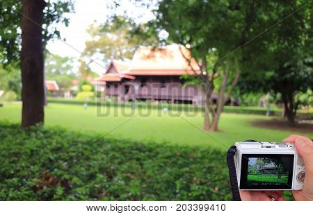 Woman'hand holding a camera for taking picture of an impressive Thai style traditional vintage house, Nakhon Pathom, Thailand