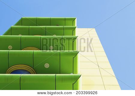 Modern green and yellow building with balconies on blue sky background. Color blocking architecture. Contemporary architecture in green and yellow colors. Colorful modern building. Color blocked hotel