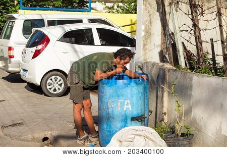 Dumaguete, Philippines - 6 August 2017: Homeless man seek food in garbage by car parking. Economic problem poverty concept. South Asia social unprotected people. Poor hungry beggar eats by trash bin