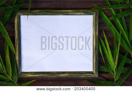Blank paper and bamboo flat lay on wooden background. Natural rustic photo frame with blank place for text. Bamboo leaf on table. Zen or beauty mockup top view. Wood frame with tropical floral decor