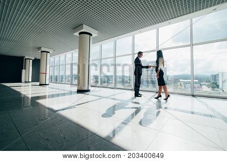 Business Man And Woman Shaking Hands With A Smile On The Background Of The Large Panoramic Windows I