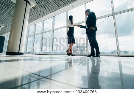 Two Smiling Young Businesspeople Shaking Hands Together In An Office Building Hallway In Front Of Wi