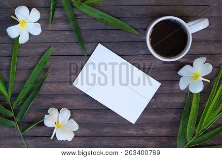 Bamboo leaf and frangipani flower on rustic wooden background. Blank card and floral decor top view. Plumeria and bamboo around white paper. Tropical wedding invitation. Beauty banner with text place