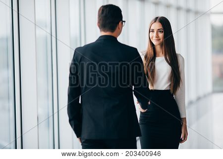 Businessman And Businesswoman Shaking Hands In Office With Big Panoramic Windows In Office