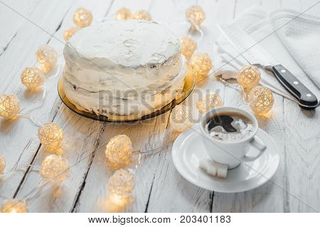 Celebration homemade biscuit cake with white cream on a white wooden table. Twinkling lights around the cake. White cup with black coffee and lump sugar on a saucer. Kitchen knife at the background.