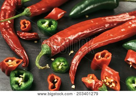 Red and green chili pepper of black slate plate. Rustic cuisine. Hot pepper of red and green color. Close-up view at red chili pepper. Cutted pieces of chili pepper