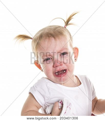 A Sad unhappy crying cute little young toddler girl wiping tears, isolated.
