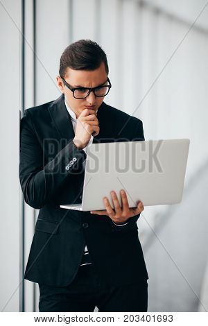 Businessman Wearing Glasses And Suit Working Laptop Holding Hands Near Panoramic Window.