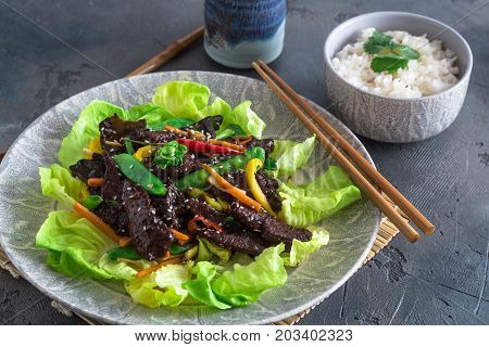 Asian stir fried chicken liver with bowl of rice and green tea, close view