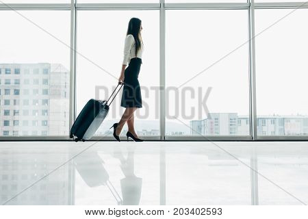 Traveler Businesswoman Waiting For Delayed Flight At Airport Lounge Standing With Luggage Watching T