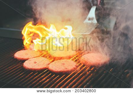 Cutlets burgers frying on a grill fire spatula