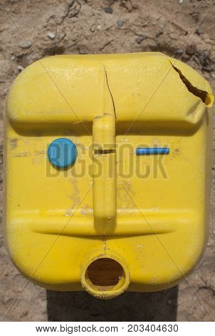Weathered used yellow plastic tube on sand background imitating funny human face