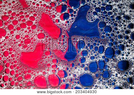Macro of bubbles in fluid on a blue and red background.