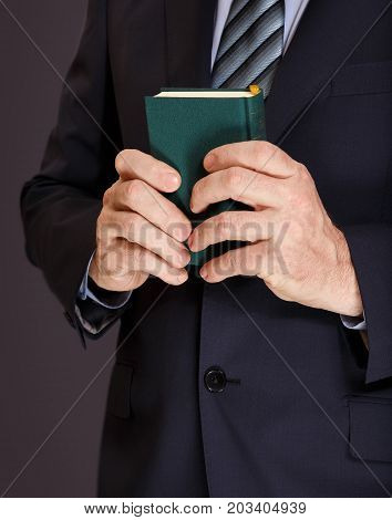 A man in a jacket holds in both hands a small book in the green cover