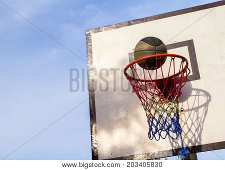 Basketball ring. Basket and ball. Accurate ball throw in basket. Street basketball. School holiday activity. Basketball competition victory. Basketball game on sunny day. Active game outdoor equipment
