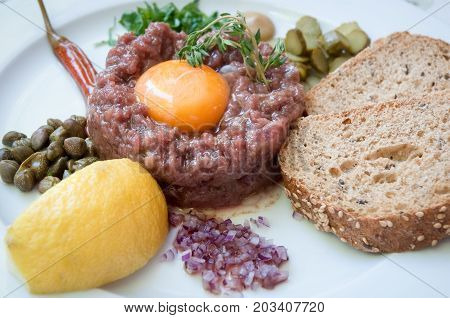 Steak tartar with raw egg yolk, rye bread and   onion, shot from above .