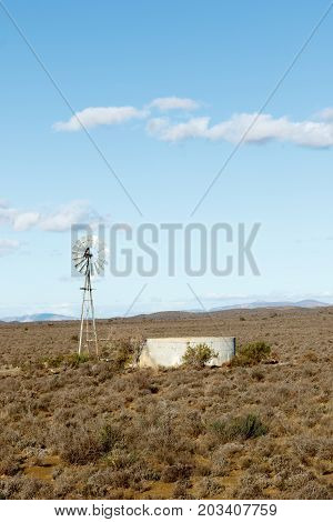 Windmill With A Dam In The Fields Of Central Karoo