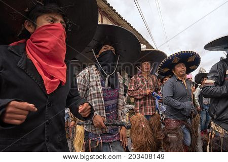 July 24 2017 Cotacachi Ecuador: indigenous men in costumes some with face covered dancing on the street at Inti Raymi