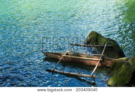 Rustic wooden boat on still water lake. Idyllic lake landscape with old catamaran boat. Summer travel to camp. Fresh water lake view. Turquoise water. Wild nature ecotourism. Holiday camping by water