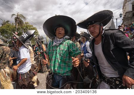 July 24 2017 Cotacachi Ecuador: indigenous kichwa men wearing large sombreros dancing on the street at Inti Raymi celebration