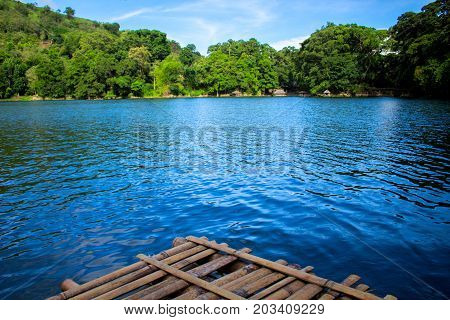Rustic wooden raft on still water lake. Idyllic lake crossing with old raft. Summer travel to mountain camp. Fresh water lake view. Turquoise water. Wild nature ecotourism. Holiday camping by water