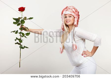 Accessories and clothes for cold days fashion romantic gestures concept. Woman in winter furry hat holding red rose