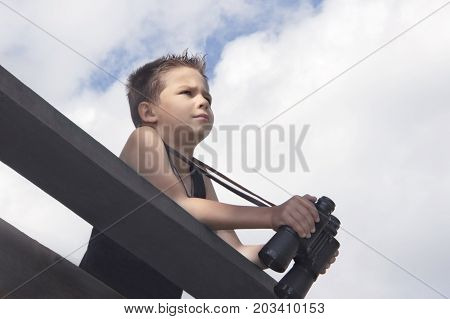 The mischievous little boy holds the binoculars in his hands and peers into the distance against the sky with clouds.toning