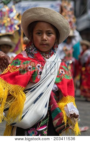 June 18 2017 Pujili Ecuador: indigenous kichwa girl dancing in the street in traditional colourful dress at Corpus Christi parade
