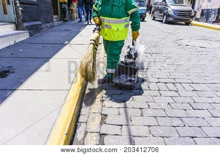 A cleaner in the street clean the dirt floor