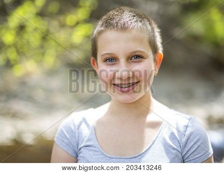 A teen with shaved head outside in forest