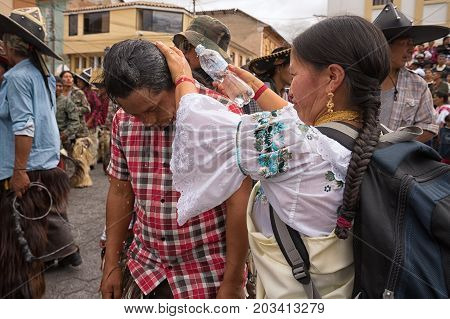 July 24 2017 Cotacachi Ecuador: indigenous kichwa woman pouring water over a man's head on the hot day of Inti Raymi celebration