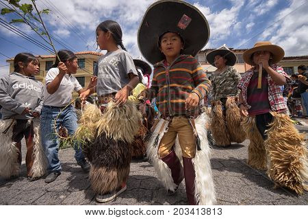July 24 2017 Cotacachi Ecuador: indigenous kichwa children wearing chaps on the street at Inti Raymi celebration