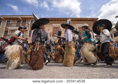 July 24 2017 Cotacachi Ecuador: indigenous kichwa men wearing a traditional chaps on the street at Inti Raymi celebration