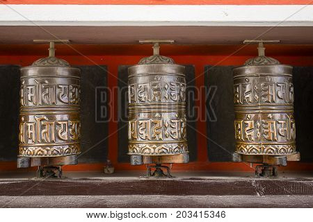 Buddhist prayer wheels in Tibetan monastery with written mantra. Himalayan village Nepal. Close up