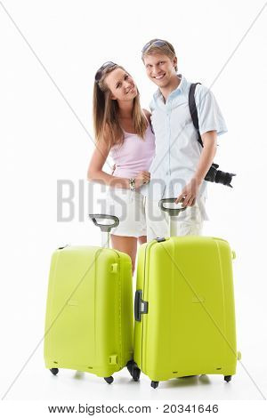 An attractive couple with their suitcases on a white background