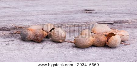 Tamarind pod with some shell broke on wooden floor selective focus.