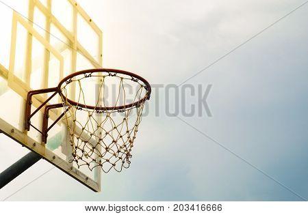 Basketball hoop and transparent backboard of warm light effect on blue sky background selective focus.
