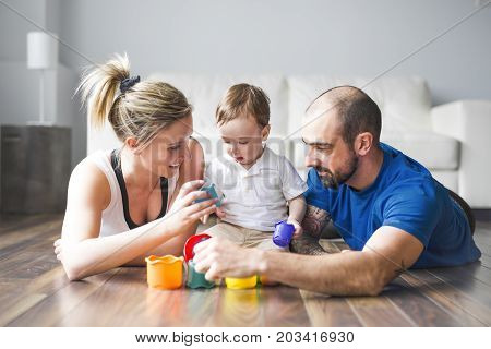 A Happy family with parents and son playing with colorful blocks in the livingroom