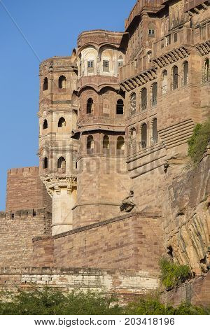 Details of Jodhpur fort at sunset. The majestic fort perched on top dominating the blue town. Scenic travel destination and famous tourist attraction in Rajasthan India.