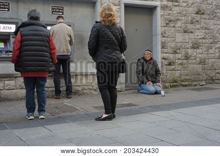 Shop Street, Galway, Ireland July 2017, Man Begging On Knees Near A To An Atm With People Withdrawin