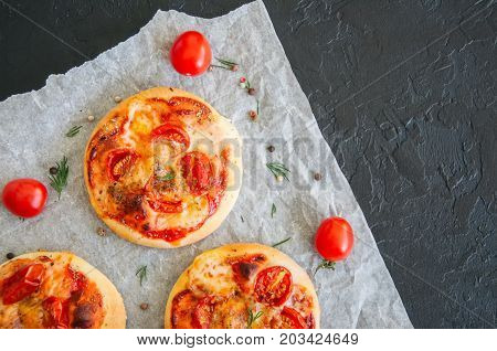 Mini Pizzas Margheritas On A Parchment Paper On A Black Stone Background. Top View With Copy Space.