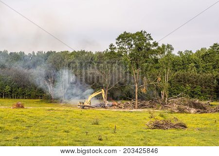 Tending a log fire with an excavator. This is done after logging has taken place to dispose of the debris.