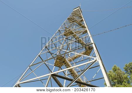 A diminishing perspective capture of a rural firetower on a clear day.
