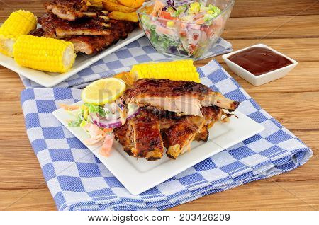 Barbecued pork ribs meal with sweetcorn and fresh salad