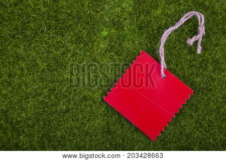 Red tag on a green grass close-up .