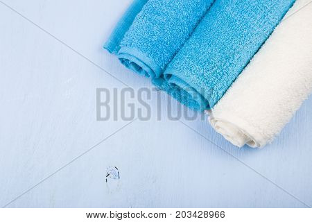Three Towels On Wooden Table.