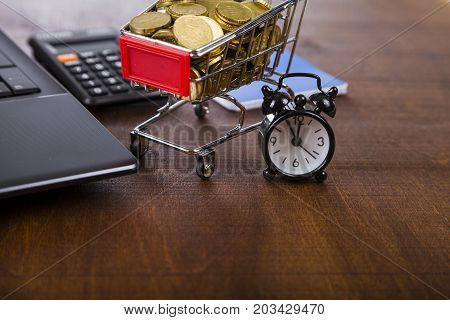 Shopping Trolley With Coins,  Laptop And Alarm Clock